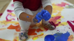 Little artist uses jar of paint with his hands - stock footage
