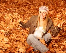 Girl throwing up autumnal leaves Stock Photos
