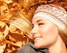 Stock Photo of cute blonde laying down on tree leaves