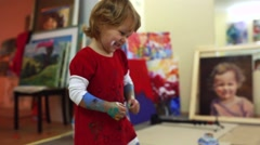 Little artist paints with jar of paint - stock footage