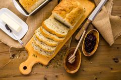 sourdough seeded bread and bowl of honey with honey dipper - stock photo