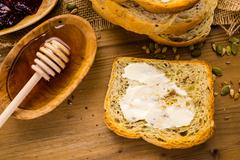 sourdough seeded bread with butter and honey dipper - stock photo