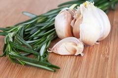 rosemary and garlic on a wooden chopping board - stock photo