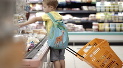 Boy putting products into shopping cart - stock footage