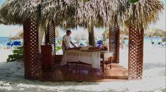 Spa treatment massage in gazebo on the beach Stock Footage