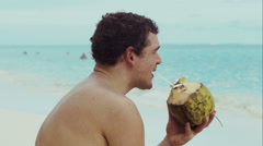 Man on the beach drinking from coconut Stock Footage