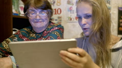 Young and senior woman looking through photos on pad Arkistovideo