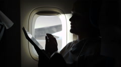 Woman sitting by illuminator in plane with touch pad Stock Footage