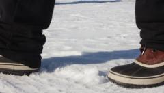 CU Boots walking across snow Stock Footage