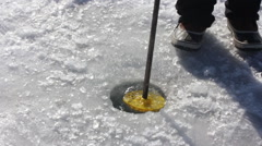 MS Scooping Ice from Fishing Hole Stock Footage