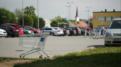 Timelapse of traffic on parking zone with empty shopping cart - stock footage