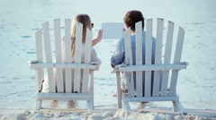 Young couple in chaise-longues holding pad and looking at it Stock Footage
