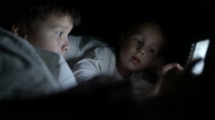 Two little boys try to watch the film at night using the tablet Stock Footage