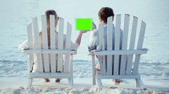 Woman and man sitting on the beach and looking at pad with green screen Stock Footage