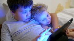 Two boys in bed with touch pad. One playing game, another watching Stock Footage