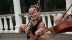 Group of female violinists play a melody on the street Stock Footage