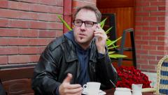 Angry man talking on the phone in sidewalk cafe Stock Footage