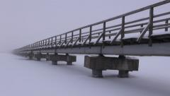 Landscape with old wooden long bridge on snowy lake ice in winter and  fog Stock Footage