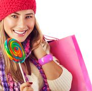 Girl lick sweets and holding pink bag Stock Photos