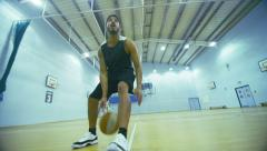 Basketball player dribbles the ball down the court Stock Footage