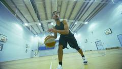 Basketball player dribbling the ball down the court Stock Footage