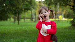 Little girl shouting into the phone in a park - stock footage