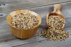 Raw rice in wooden kitchenware spilling onto rustic wood Stock Photos