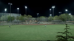 Evening Softball Game Under the Lights Stock Footage
