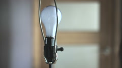 Swapping Out Incandescent for LED Bulb - stock footage