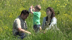 Stock Video Footage of Family sitting on green meadow laughing, child arrange his cap on father head 4K