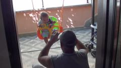 Adult taking photo of child on swing 2 Stock Footage