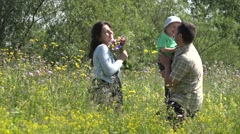 Happy family, parents and child dancing in spring meadow  - stock footage