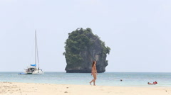 People walking along  beach on background of yacht and island Stock Footage
