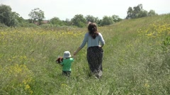 Mother and baby with teddy bear toy holding hands move away on spring meadow  Stock Footage