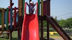 Little boy slide on child playground  Stock Footage