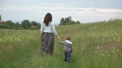Mother and son walking together on spring meadow, birds flying 4K Stock Footage
