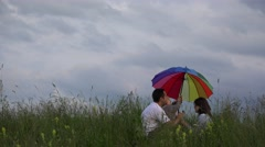 Parents and little child sitting on spring meadow play with colored umbrella 4K Stock Footage