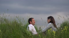 Attractive couple resting on spring meadow close sky, talking, dreaming 4K Stock Footage