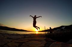 silhouette of a girl jumping at sunset on the beach - stock photo