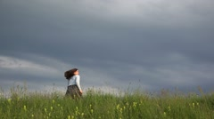 Couple of lovers running on spring hill, man caching woman, dramatic sky  - stock footage