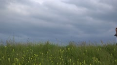 Beautiful family walking on spring hill, piggy ride, dramatic sky  Stock Footage