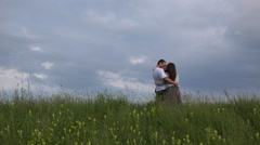 Young family standing on spring hill close to dramatic sky admiring  - stock footage