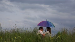 Happy  parents with colored umbrella, lovely child coming, dramatic sky  Stock Footage