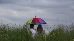 Couple in love, colored umbrella, close to sky  Stock Footage