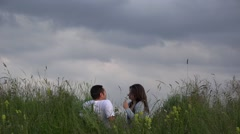 Couple sitting on spring meadow close sky, have fun, smiling, enjoy flower  Stock Footage
