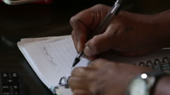 Dark-skinned man  writing notes with pan Stock Footage