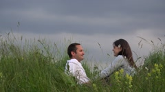 Attractive couple resting on spring meadow close sky, talking, dreaming  Stock Footage