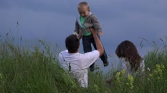 Portrait of happy family in nature, spring field close blue sky  - stock footage