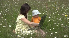 Young mother and little boy looking together to tablet in nature, flowers 4K - stock footage