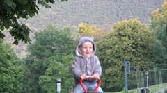 Lovely child in a rocking chair in park, mountain in background  Stock Footage